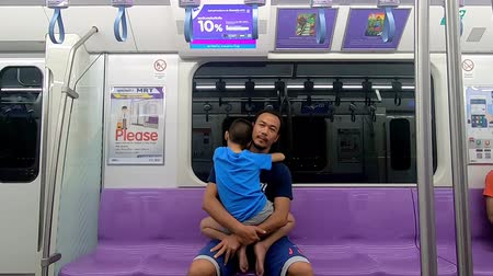 Father carries his son asleep sitting on the trains at sky train station, Nonthaburi in Thailand July 6, 2019 Archivo de Video
