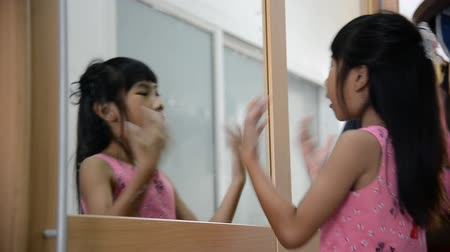 tükör : Asian girl dressing and playing at mirror Stock mozgókép