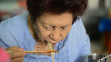 ramen : Asian senior woman eating noodle soup at local restaurant