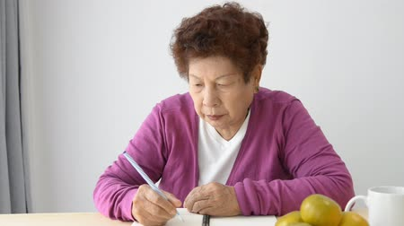 banknoty : Home finance, personal savings, and financial planning, old Asian woman checking bills and doing budge. Wideo