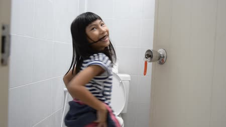 sanitário : Happy Asian girl using toilet at home.