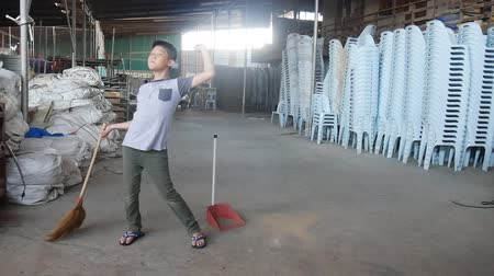 swabber : Asian boy sweeping the family factory, small business