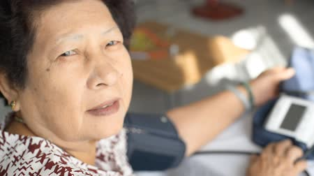 starość : Asian senior woman checking blood pressure at home Wideo