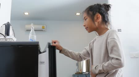 lodówka : Girl open refrigerator and pouring water into a glass.