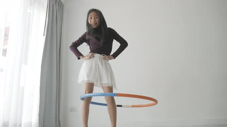delikanlı : Asian girl playing a hoop near window at home
