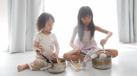 cooking pots : Asian cute children sitting on the kitchen floor, Stock Footage