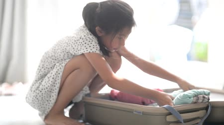 Happy girl is packing a luggage for a new journey. Wideo
