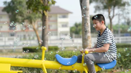 boyhood : Happy boy playing seesaw outdoor with bubble, lifestyle concept