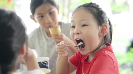 Happy Asian children eating ice cream in cafe together