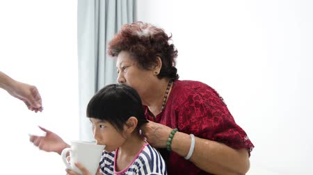 braid hair : Asian girl drinking a cup of water while her grandmother braiding her hair. Stock Footage