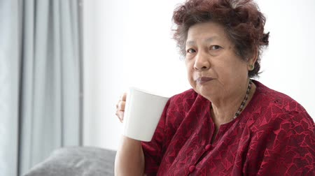 greater : Asian senior woman drinking a cup of water at home Stock Footage