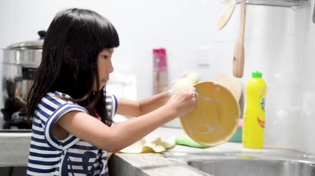 pia : Asian girl washing dish in kitchen at home, lifestyle concept.