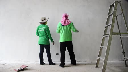 sander : PRACHUAP KHIRI KHAN, THAILAND - SEPTEMBER 21, 2015: Workers sanding Plaster Wall at Hua Hin, Thailand