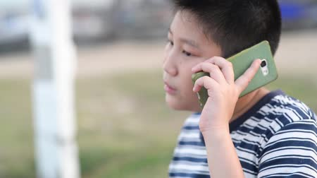 boyish : Asian boy make a phone call outdoor.