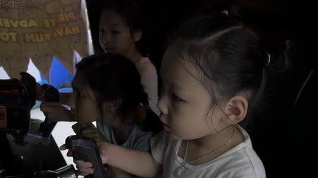 atirador : PRACHUAP KHIRI KHAN, THAILAND - MARCH 04, 2018: Untitled children group playing shooter video game in game center together