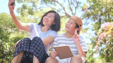 Asian mother and son sitting in the park outdoor and selfie with smartphone together, family lifestyle concept Wideo
