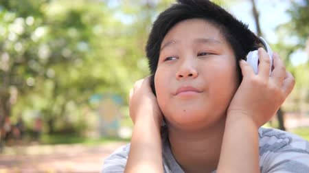 Cheerful Asian preteen boy with headphone sitting in the park outdoor