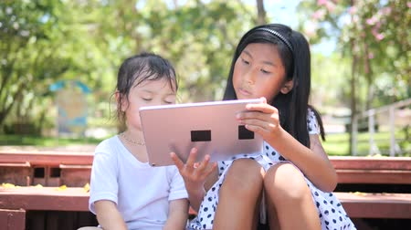 Happy children playing tablet together outdoor.