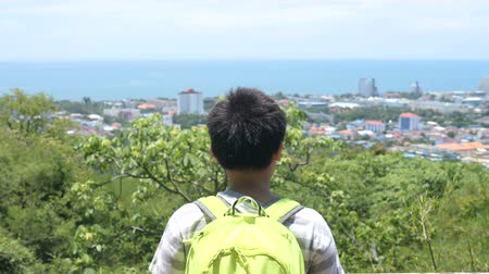 viewpoint : Back of backpack boy at Hua Hin view point looking at coastline in sunny day. Stock Footage