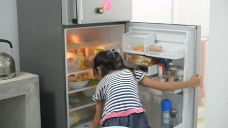 completo : Asian girl open refrigerator and looking for something, take it and close the door.