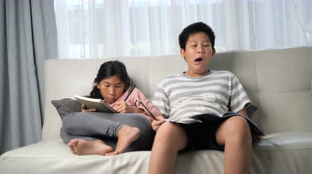 çizgi roman : Asian kids reading their book at home. Boy yawning and feeling sleepy, slow motion. Stok Video
