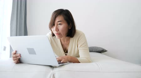 přední : Asian woman lying on bed and using laptop at home, slow motion.