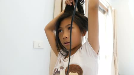 after school : Asian girl using hair dryer at home. Stock Footage