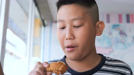 nugget : Asian child enjoys eating fried chicken