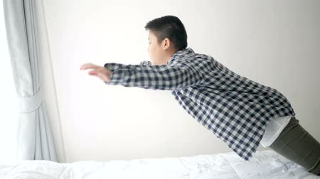 mischief : Asian preteen boy jumping on bed, slow motion