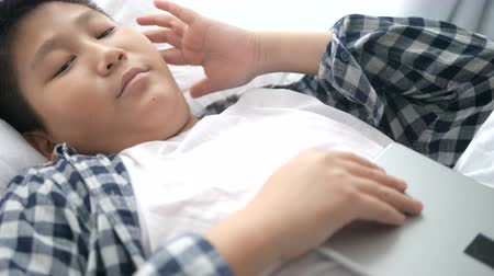 hidden face : Asian boy sleeping and holding tablet with him Stock Footage