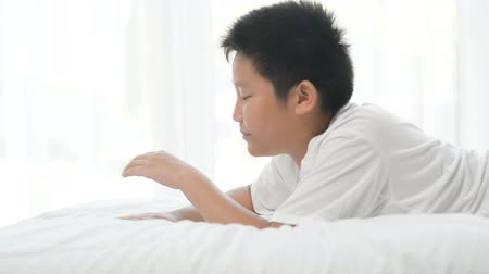 minder : Happy Asian preteen boy lying on bed and using laptop.