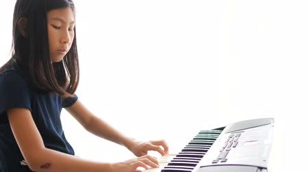 dizgi : Child girl playing on an electronic keyboard instrument. Stok Video