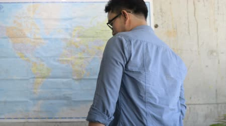 directional : Happy Asian tourist man planning for next destination with world map on wall