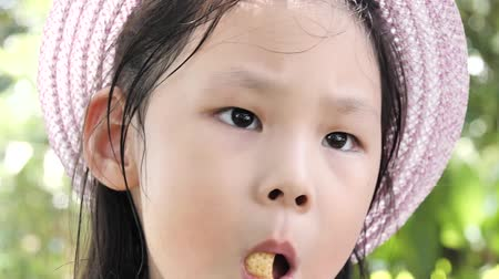 Happy Asian girl wearing hat and eating some snack in the park outdoor, slow motion.