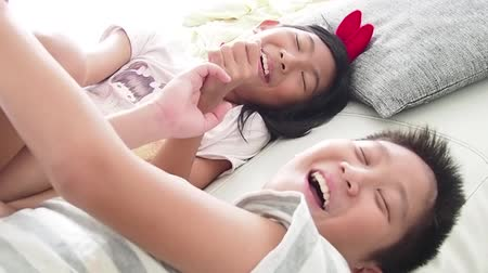 Happy Asian preteen boy hugging and playing his younger sister on bed at home. Wideo