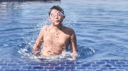 Asian boy wearing goggles and swimming in pool in sunny day.