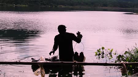 Silhouette of fisherman diving up from water and holding his fishes.