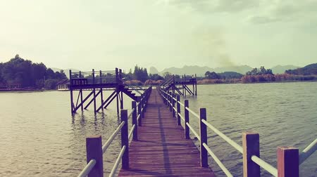 curso : Walking through wooden bridge over water lake, point of view.