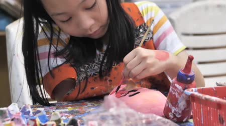 tynk : Asian girl painting plaster mask in artist workshop, lifestyle concept.