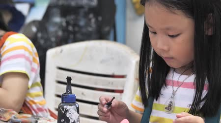 Asian girl painting plaster mask in artist workshop, lifestyle concept.