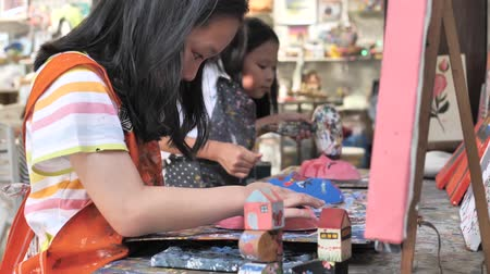 Asian girl painting plaster mask in artist workshop and make it dry with hair dryer, lifestyle concept.