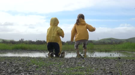 küçük kız : Kids in rain boots jumping happily in puddle Stok Video
