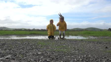 резина : Kids in rain boots jumping happily in puddle Стоковые видеозаписи