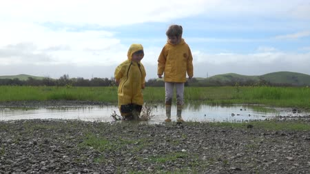 razem : Kids in rain boots jumping happily in puddle Wideo