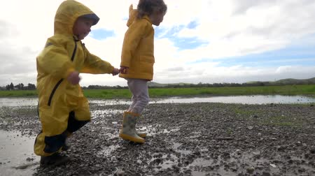 buty : Kids in rain boots jumping happily in puddle Wideo