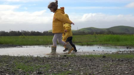 salto : Kids in rain boots jumping happily in puddle Stock Footage
