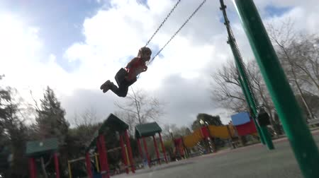 plac zabaw : Slow motion of happy girl swinging on the playground