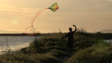 despreocupado : Slow motion silhouette of boy running with kite at sunset Stock Footage