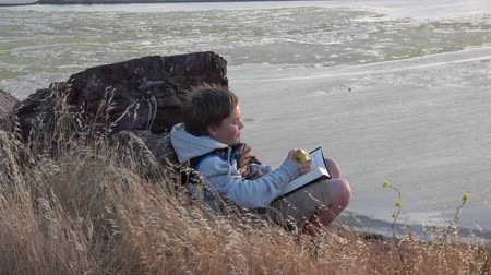 Boy sitting outside reading book eating apple at sunset