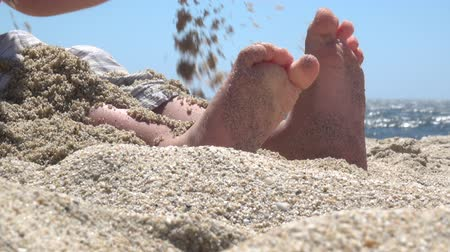 Childs bare feet in sand on beach Stok Video
